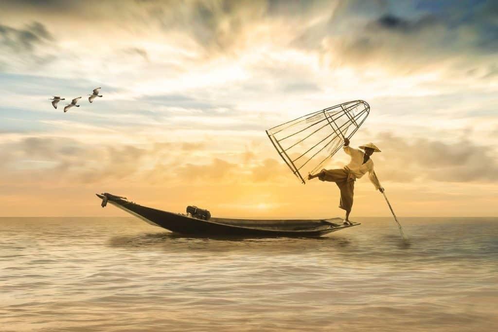 Рыбак, балансирующей на краю лодки, держащий ловушки для рыбы над головой и шест, упирающийся в воду