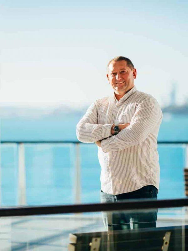 Николай Рысёв, автор книг по продажам и управлению, стоит на фоне моря